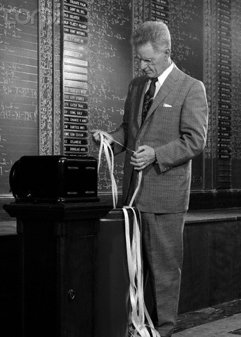 1950s 1960s Stock Broker Reading Quotation Tape At Office Ticker-Tape Machine On Exchange